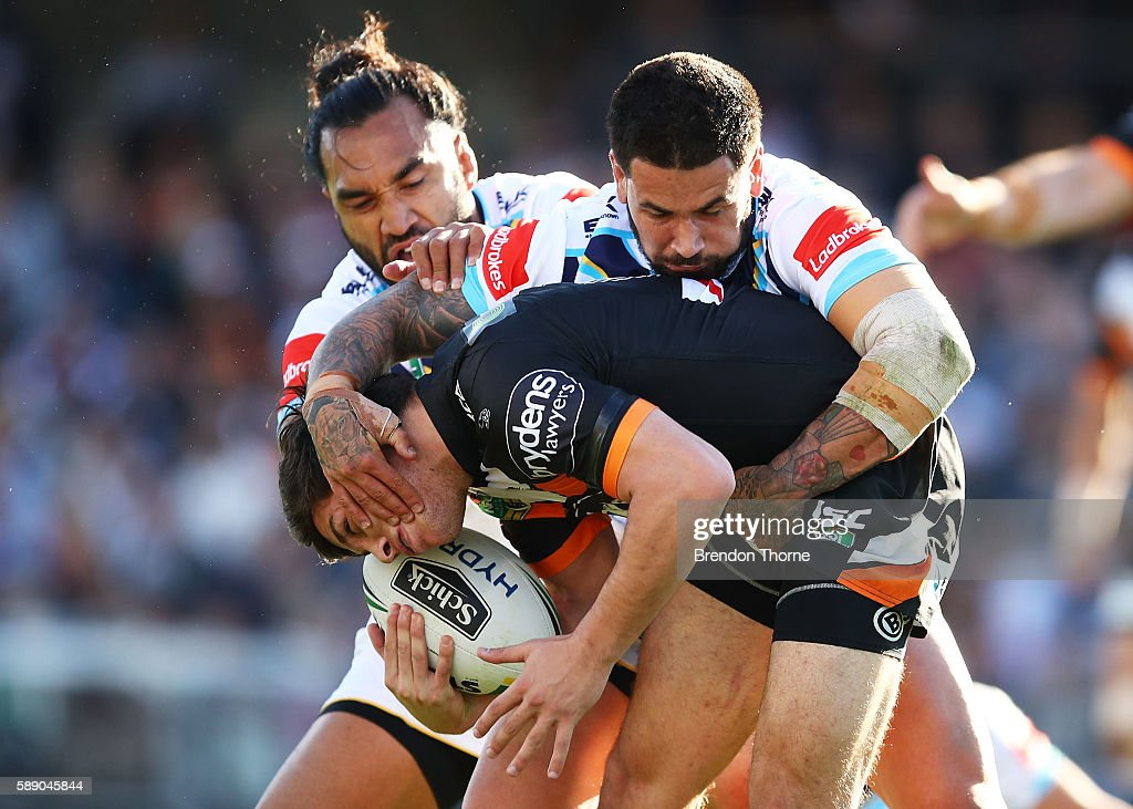 Mitchell Moses of the Tigers is tackled by the Titans defence during the round 23 NRL match between the Wests Tigers and the Gold Coast Titans at Campbelltown Sports Stadium on August 13, 2016 in Sydney, Australia.