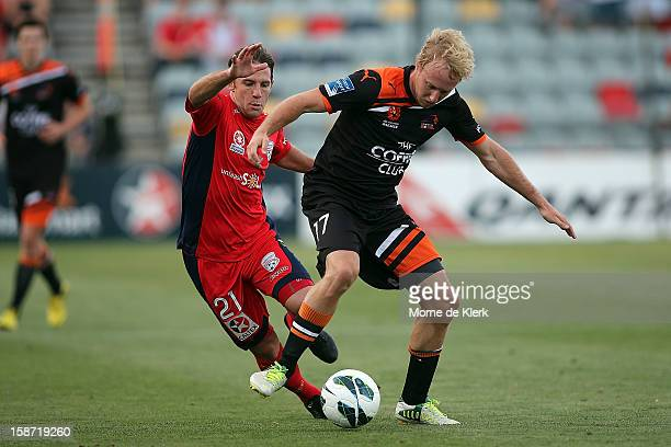 Mitchell Nichols of Brisbane is brought down by Jeronimo Neumann of Adelaide during the round 13 ALeague match between Adelaide United and the...
