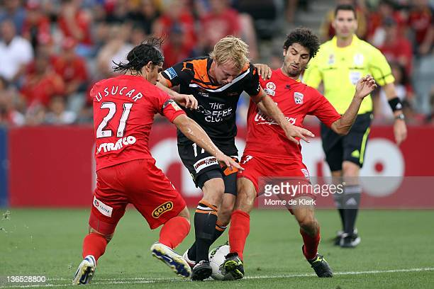 Mitchell Nichols of the Roar is bocked by Adelaide defenders during the round 14 ALeague match between Adelaide United and the Brisbane Roar at...