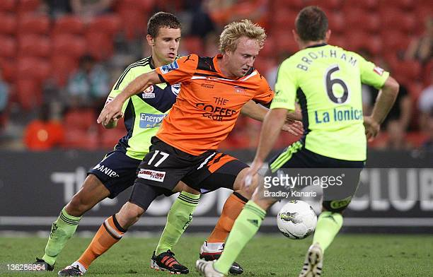 Mitchell Nichols of the Roar is pressured by the defence during the round 13 ALeague match between the Brisbane Roar and the Melbourne Victory at...