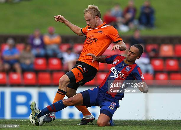Mitchell Nichols of the Roar is tackled by Tarek Elrich of the Jets during the round 24 ALeague match between the Newcastle Jets and the Brisbane...