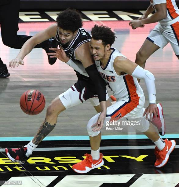 Mitchell of the Santa Clara Broncos and Colbey Ross of the Pepperdine Waves chase after a loose ball during the West Coast Conference basketball...