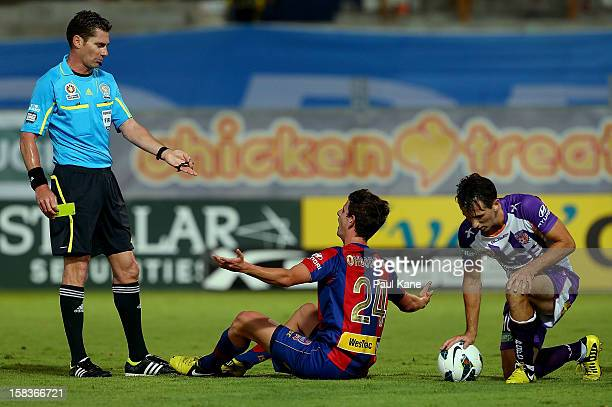 Mitchell Oxborrow of the Jets questions referee Ben Williams as Liam Miller of the Glory looks on during the round 11 ALeague match between the Perth...