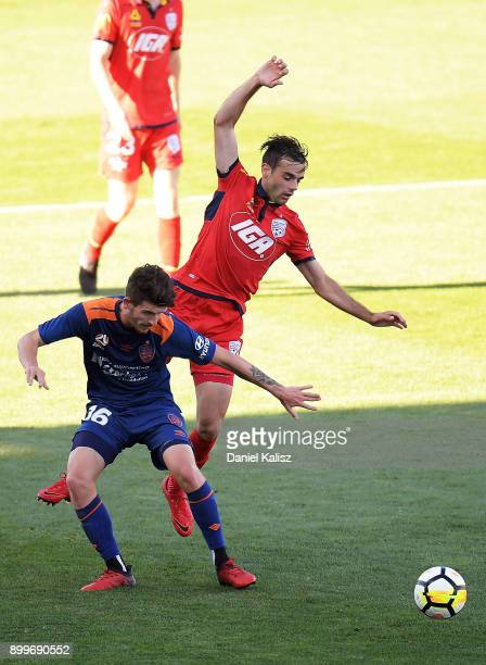 Mitchell Oxborrow of the Roar and Nikola Mileusnic of United competes for the ball during the round 13 ALeague match between Adelaide United and...