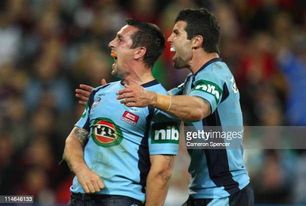 Mitchell Pearce of the Blues celebrates a try with team mate Michael Ennis during game one of the ARL State of Origin series between the Queensland...