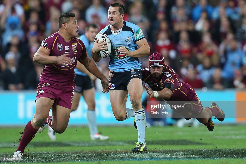 Mitchell Pearce of the Blues is tackled by Johnathan Thurston of the Maroons during game two of the ARL State of Origin series between the Queensland Maroons and the New South Wales Blues at Suncorp Stadium on June 26, 2013 in Brisbane, Australia.