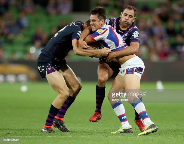 Mitchell Pearce of the Knights is tackled by Ryan Hoffman and Cameron Smith of the Storm during the round six NRL match between the Melbourne Storm...