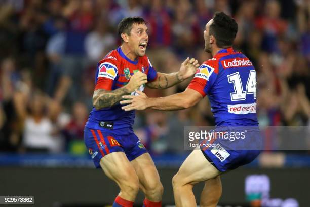 Mitchell Pearce of the Knights kicks a field goal in golden point and celebrates with team mate Brock Lamb during the round one NRL match between the...