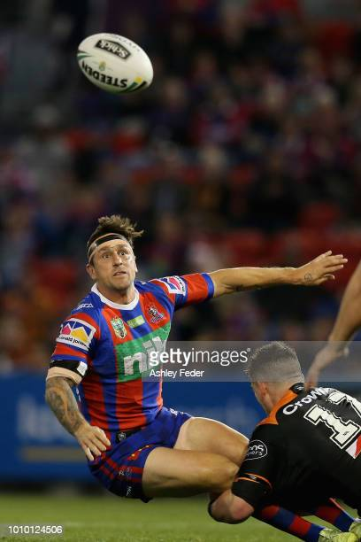 Mitchell Pearce of the Knights offloads the ball during the round 21 NRL match between the Newcastle Knights and the Wests Tigers at McDonald Jones...