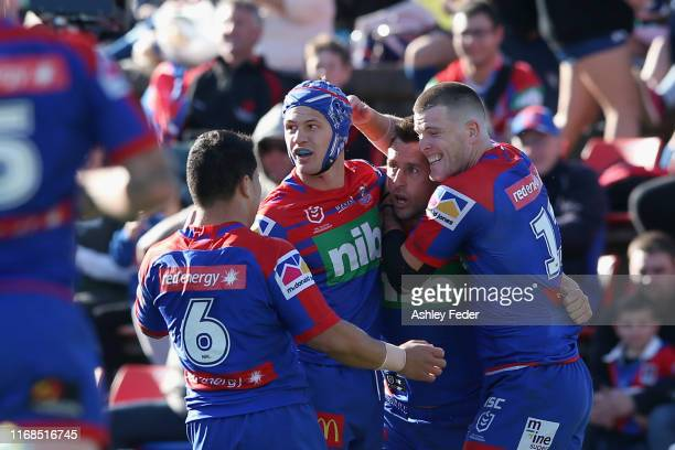 Mitchell Pearce of the Newcastle Knights celebrates his try with team mates during the round 22 NRL match between the Newcastle Knights and the North...