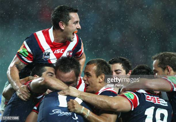 Mitchell Pearce of the Roosters celebrates victory with his teammates during the round 24 NRL match between the Sydney Roosters and the Cronulla...