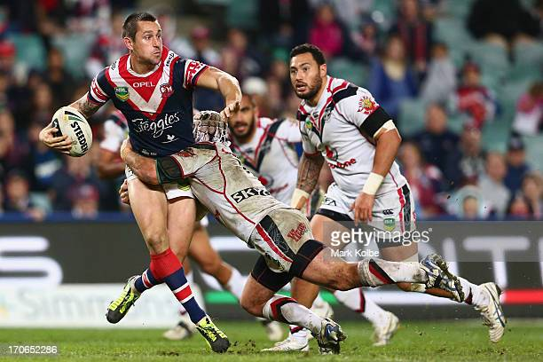 Mitchell Pearce of the Roosters gets a pass away as he is tackled during the round 14 NRL match between the Sydney Roosters and the New Zealand...