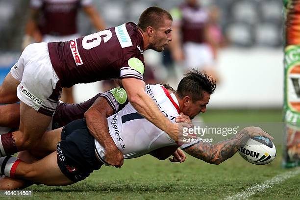 Mitchell Pearce of the Roosters scores a try with Kieran Foran of Manly tackling behind during the NRL Trial Match between the Sydney Roosters and...