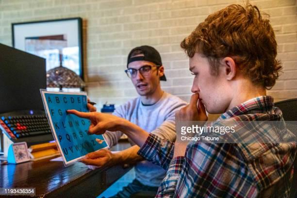 Mitchell Robins de 16 años señala las letras para formar palabras que el terapeuta Anthony Bartell de 23 años puede escribir para preparar un texto...