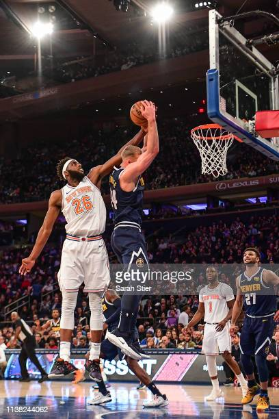 Mitchell Robinson of the New York Knicks attempts to block Mason Plumlee of the Denver Nuggets from scoring during the second half of the game at...