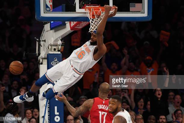 Mitchell Robinson of the New York Knicks swings from the rim after making a slam dunk during the second quarter of the game against the Houston...