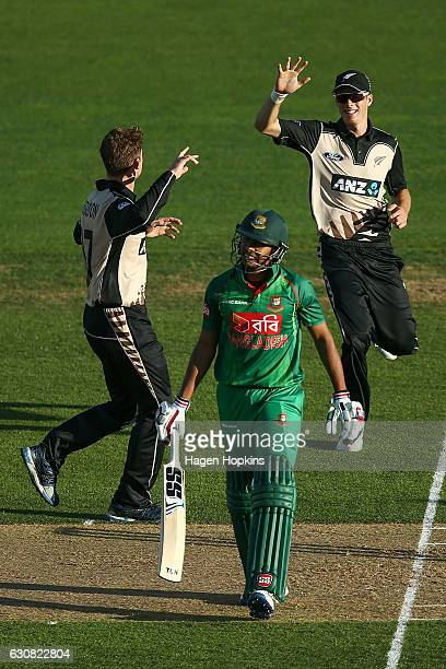 Mitchell Santner and Lockie Ferguson of New Zealand celebrate the wicket of Soumya Sarkar of Bangladesh during the first Twenty20 match between New...