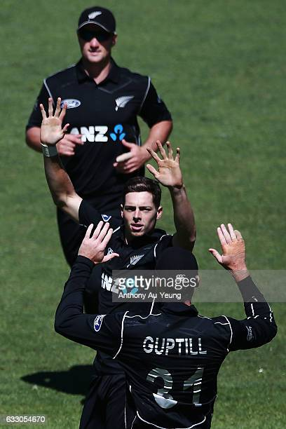 Mitchell Santner celebrates with teammates for the wicket of Shaun Marsh of Australia during the first One Day International game between New Zealand...