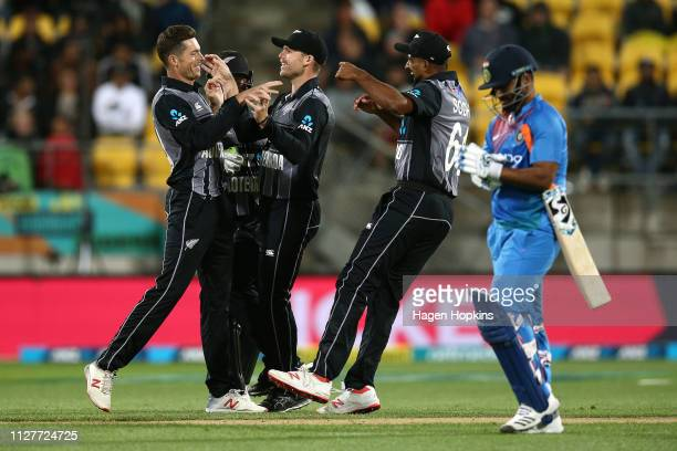 Mitchell Santner of New Zealand celebrates with Lockie Ferguson and Ish Sodhi after taking the wicket of Rishabh Pant of India during game one of the...