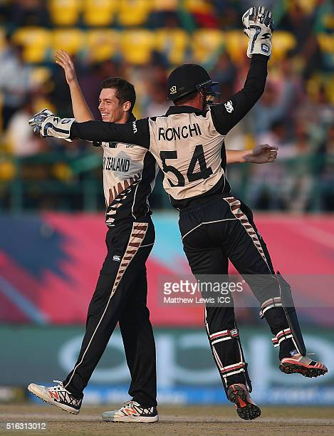 Mitchell Santner of New Zealand is congratulated by Luke Ronchi of New Zealand on the wicket of David Warner of Australia after he was caught by...