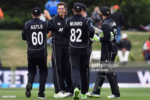 Mitchell Santner of New Zealand is congratulated by team mates after dismissing Rovman Powell of the West Indies during the One Day International...