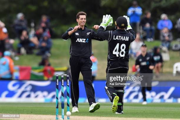 Mitchell Santner of New Zealand is congratulated by Tom Latham of New Zealand after dismissing Rovman Powell of the West Indies during the One Day...
