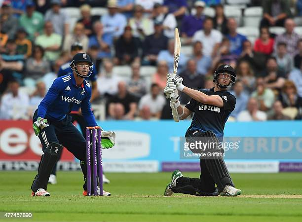 Mitchell Santner of New Zealand smashes the ball to the boundary in front of Jos Butler of England during the 4th ODI Royal London OneDay...