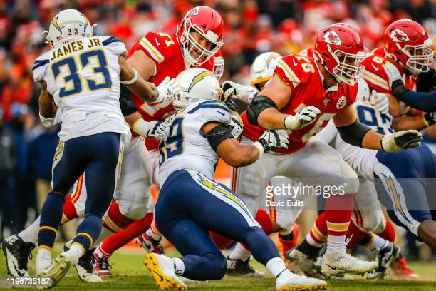 Mitchell Schwartz of the Kansas City Chiefs blocks Jerry Tillery of the Los Angeles Chargers during the fourth quarter as Laurent DuvernayTardif of...