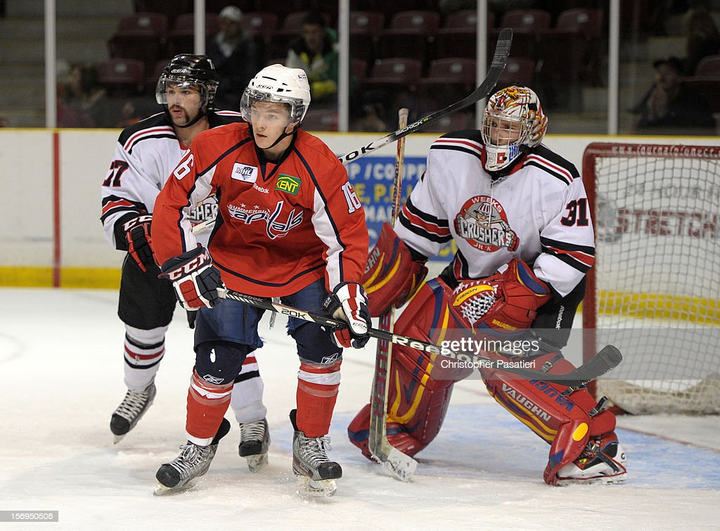 Mitchell Shewfelt #77 of the Weeks Crushers checks Colton Parsons #16 of the Summerside Western Capitals as they screen goaltender Brandon Thibeau #31 of the Weeks Crushers during the third period on November 25, 2012 at the Consolidated Credit Union Place in Summerside, Prince Edward Island, Canada.
