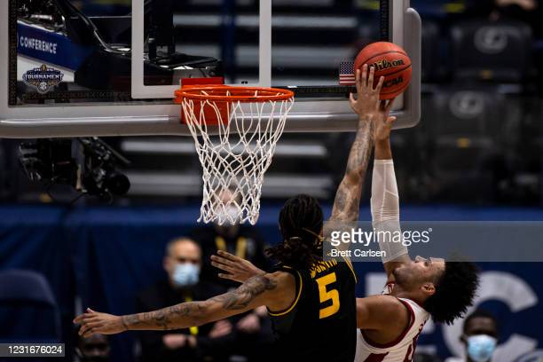 Mitchell Smith of the Missouri Tigers blocks a shot as he fouls Justin Smith of the Arkansas Razorbacks during the first half of their quarterfinal...