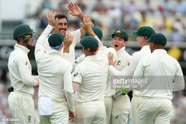 Mitchell Starc celebrates with David Warner after taking a catch to dismiss Jake Ball of England during day two of the First Test Match of the...