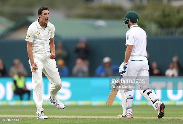 Mitchell Starc of Australia celebrates after taking the wicket of Stephen Cook of South Africa during day one of the Second Test match between...