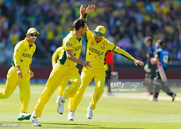 Mitchell Starc of Australia celebrates after with captain Michael Clarke after bowling Brendon McCullum of New Zealand during the 2015 ICC Cricket...