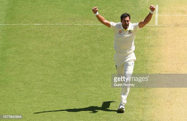 Mitchell Starc of Australia celebrates getting the wicket of Murali Vijay of India during day one of the First Test match in the series between...