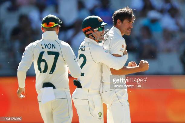 Mitchell Starc of Australia celebrates the dismissal of Mayank Agarwal of India during day one of the Second Test match between Australia and India...