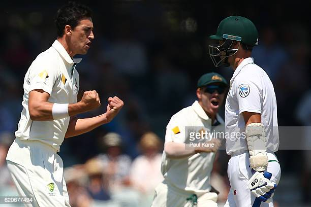 Mitchell Starc of Australia celebrates the wicket of Stephen Cook of South Africa during day one of the First Test match between Australia and South...