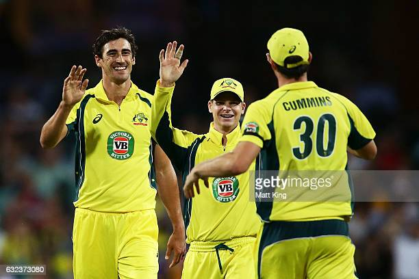 Mitchell Starc of Australia celebrates with Steve Smith and Pat Cummins after taking the wicket of Umar Akmal of Pakistan during game four of the One...