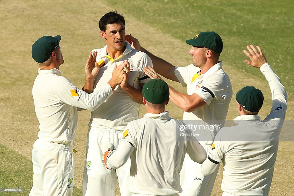 Mitchell Starc of Australia celebrates with team mates after dismissing Murali Vijay of India during day three of the 2nd Test match between Australia and India at The Gabba on December 19, 2014 in Brisbane, Australia.