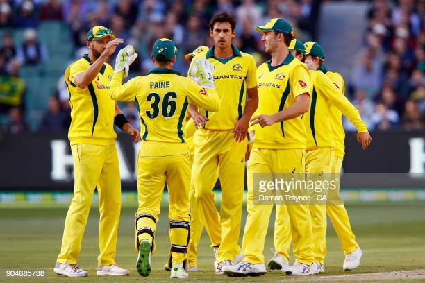 Mitchell Starc of Australia celebrates with team mates after taking the wicket of Jonny Bairstow of England during game one of the One Day...