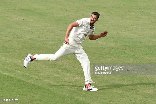 Mitchell Starc of Australia fields off his own bowling during day five of the 4th Test Match in the series between Australia and India at The Gabba...