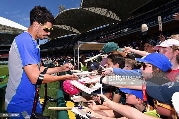 Mitchell Starc of Australia signs autographs for cricket fans prior to the start of play during day three of the Third Test match between Australia...