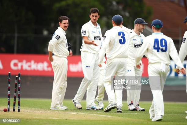 Mitchell Starc of the Blues celebrates with his team after bowling Jason Behrendorff of the Warriors to claim the first of his three wickets in his...