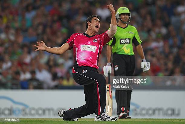 Mitchell Starc of the Sixers celebrates taking the wicket of Daniel Smith of the Thunder during the T20 Big Bash League match between the Sydney...