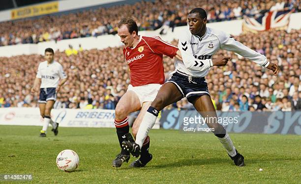 Mitchell Thomas of Spurs challenges Mike Phelan of Manchester United during a League Divsion One match at White Hart Lane on April 21 1990 in London...