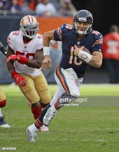 Mitchell Trubisky of the Chicago Bears runs for yardage in front of Elvis Dumervil of the San Francisco 49ers at Soldier Field on December 3 2017 in...