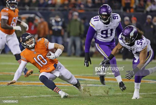 Mitchell Trubisky of the Chicago Bears slides down as Eric Kendricks and Stephen Weatherly of the Minnesota Vikings close in at Soldier Field on...