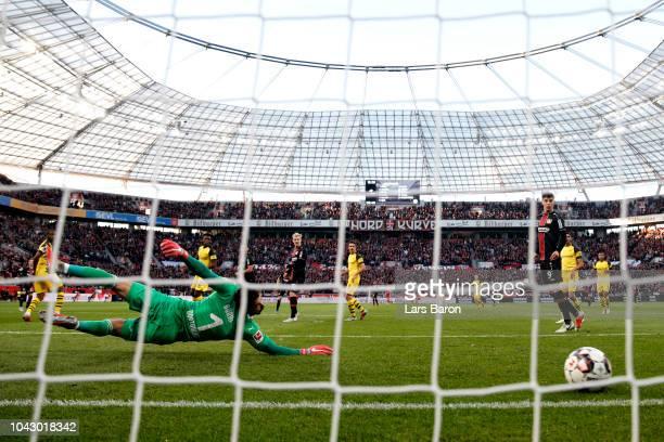 Mitchell Weiser of Bayer 04 Leverkusen scores the opening goal past goalkeeper Roman Buerki of Borussia Dortmund looks on dejected during the...