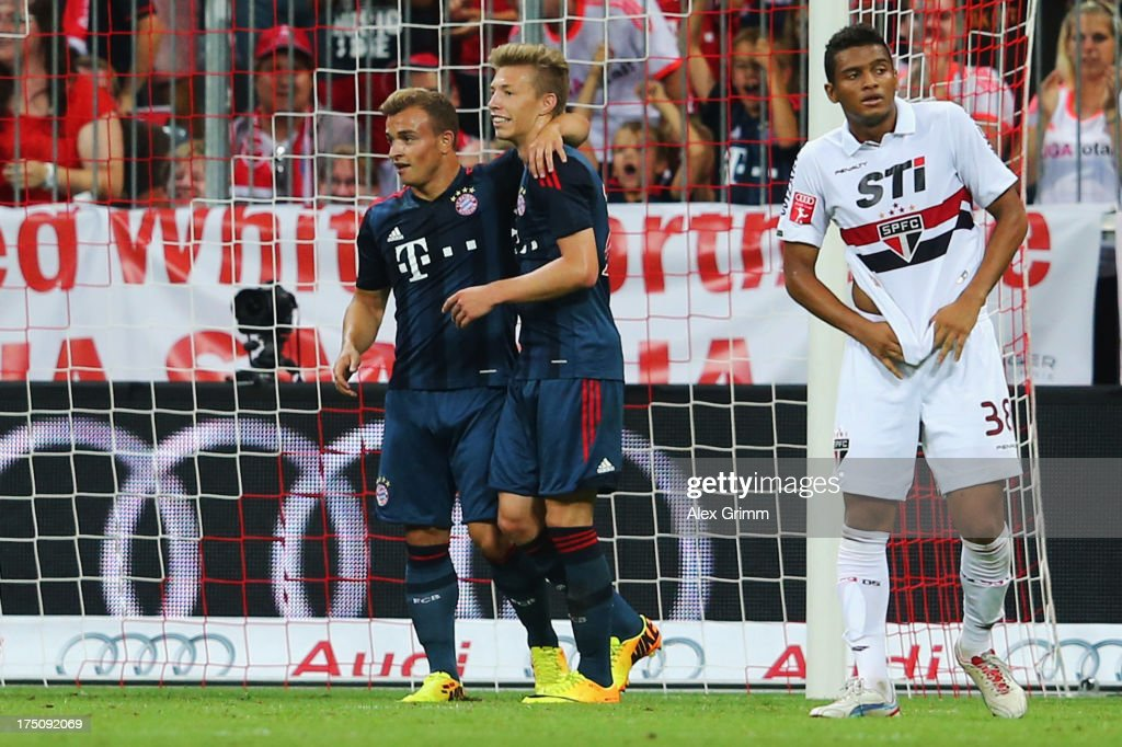 Mitchell Weiser of Muenchen celebrates his team's second goal with team mate Xherdan Shaqiri as Reinaldo of Sao Paulo reacts during the Audi Cup match between FC Bayern Muenchen and FC Sao Paulo at Allianz Arena on July 31, 2013 in Munich, Germany.