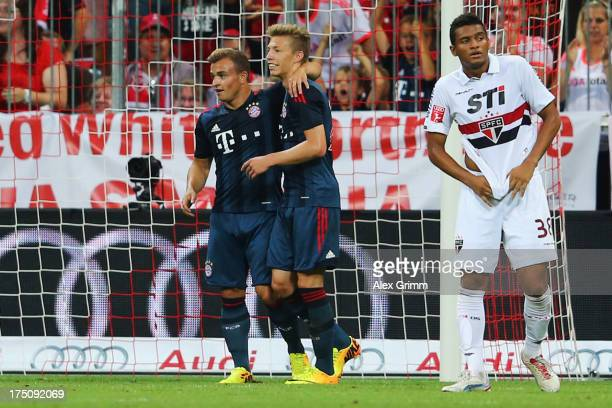 Mitchell Weiser of Muenchen celebrates his team's second goal with team mate Xherdan Shaqiri as Reinaldo of Sao Paulo reacts during the Audi Cup...