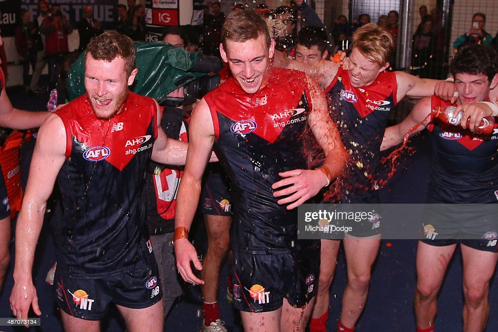 Mitchell White of the Demons (L) and Oscar McDonald sing the club song after winning their first game ever during the round 23 AFL match between the Melbourne Demons and the Greater Western Sydney Giants at Etihad Stadium on September 6, 2015 in Melbourne, Australia.